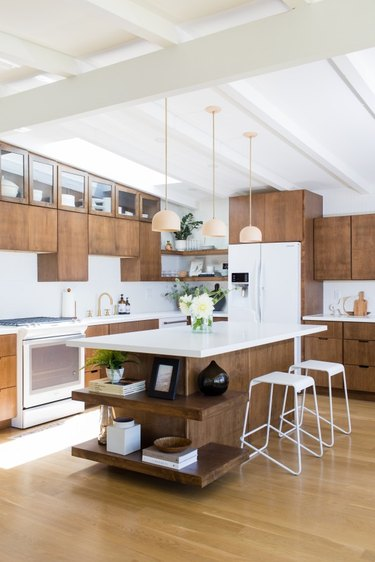 Midcentury kitchen island idea with wood cabinets and white countertops