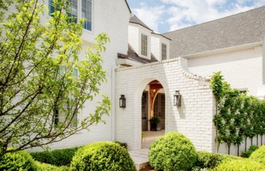 painting exterior brick on 0ff-white painted brick house, arched entry, plants, tree, hedge.