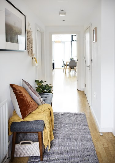 small hallway with bench and baskets for shoes