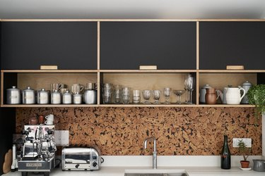 cork kitchen backsplash with black cabinets and white countertop