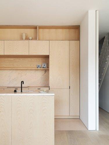 stone and wood kitchen backsplash with wood cabinets