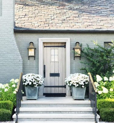 painting exterior brick with pale green on home with faded wood door, matching outdoor sconces, flowered plants in pots.