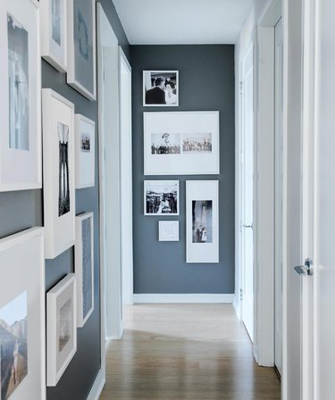 gallery wall in small hallway with wood flooring