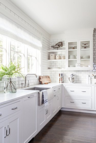 kitchen cabinet style with white glass front upper cabinets and white lower cabinets with white subway tile backsplash