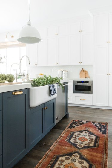 kitchen cabinet style with blue shaker cabinets and farmhouse sink with rug on floor
