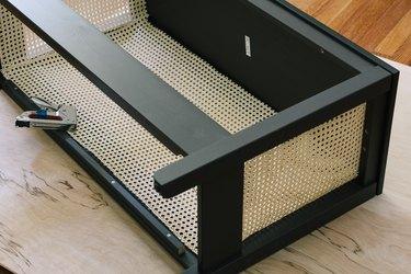 Cane webbing stapled inside IKEA console table