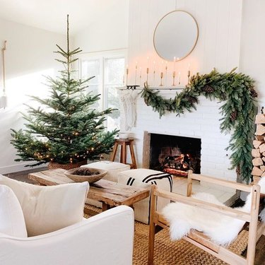 rustic Christmas tree idea with string lights in living room next to fireplace