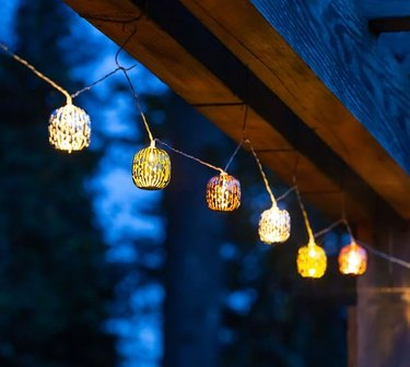 mixed-metal string lights hanging from a wood beam outside at dusk