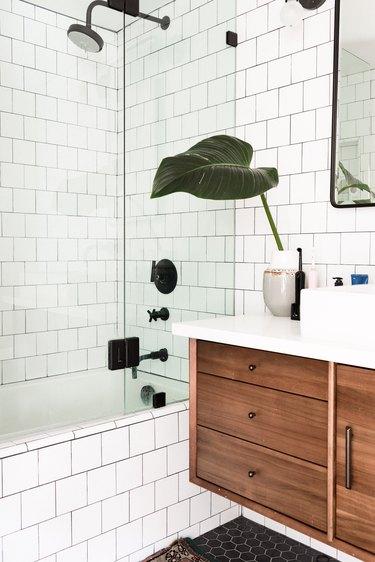 white subway tile on walls and side of bathtub, glass shower door, black showerhead, faucet and handles, wood floating vanity, black hexagon floor tile
