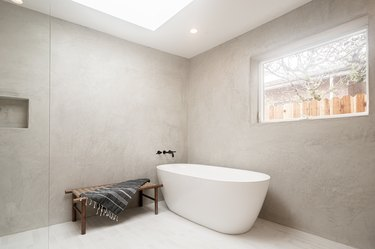 white freestanding tub in open shower space, wall-mounted black faucet and handles, small brown bench with towel draped over, glass shower door