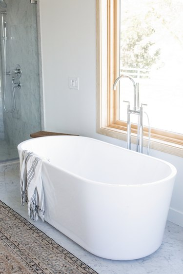white freestanding tub with striped towel draped over, floor-mounted silver faucet, large window, brown area rug, glass shower door