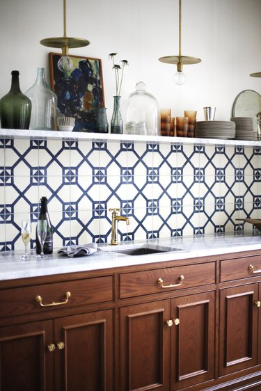 kitchen with blue backsplash and marble counters