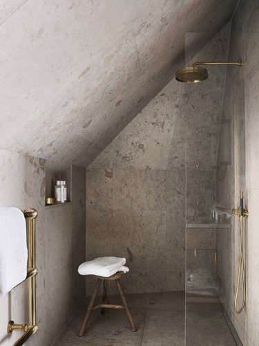 minimal rustic shower tile in in bathroom with half glass shower door and wood stool