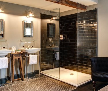 glossy black rustic shower tile in bathroom with wood beams and penny floor tile