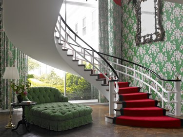 staircase with red steps and green couch nearby