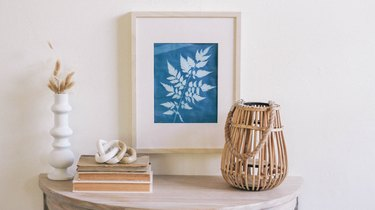 Framed blue sun print hung on wall above table with white vases, dried flowers, books and a rattan candle holder