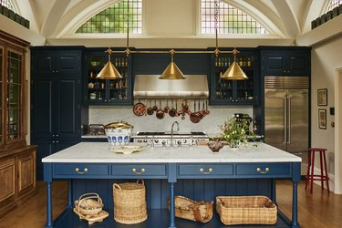 arts and crafts kitchen with blue island and brass light fixture