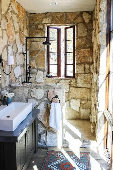 stone rustic shower tile in bathroom with white sink and black fixtures