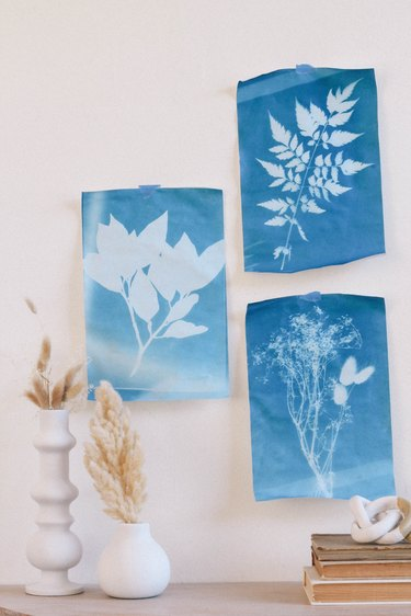 Three blue sun prints hung on wall with tape above table with white vases and books
