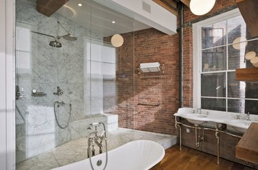 marble rustic shower tile in bathroom with brick wall and wood floor
