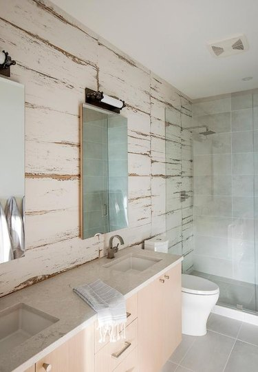 square rustic shower tile in bathroom with wood panels and wall-mounted sink