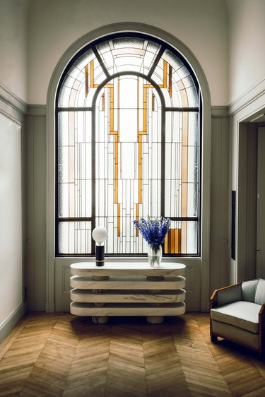 arched art deco stained glass window in front of modern console table
