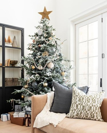 white living room with large Scandinavian Christmas tree with lots of toys, sofa with pillows