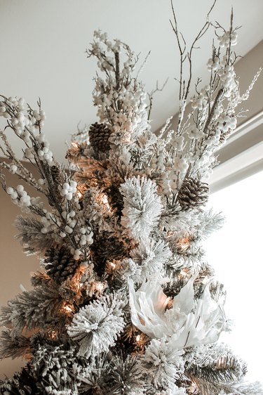 Rustic Christmas tree with pinecones, white flowers, and branches
