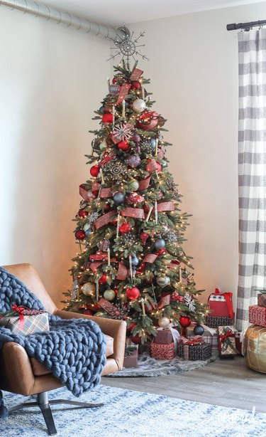Christmas Tree Themes with Rustic style Christmas tree decorated with red and multi colored ornaments, leather lounge chair, gray and white checked curtain.