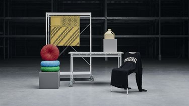 space showing items like a pile of poufs, a table, and a shirt on a chair