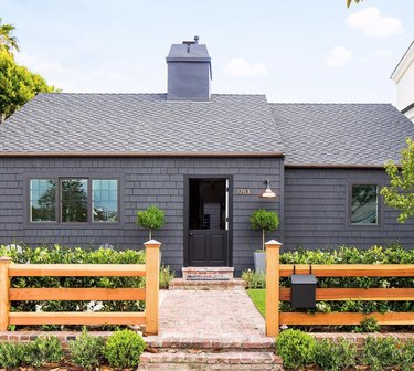 gray house with black exterior Dutch door and wood fence