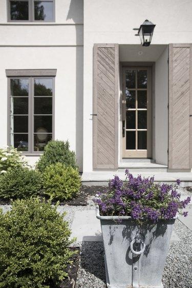 Beige exterior house shutters framing front doorway