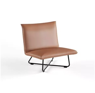 Minimal armless beige leather accent chair with black criss-crossed base