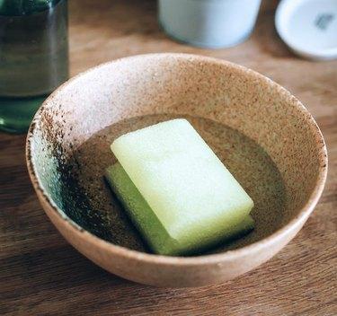 Sponge sitting in water in ceramic bowl.