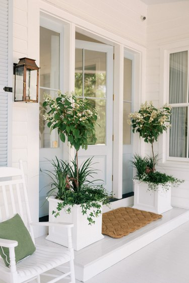 White and light blue farmhouse exterior colors on front porch
