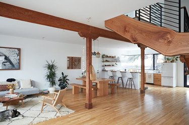 live-edge wood staircase in an open-concept living and kitchen area