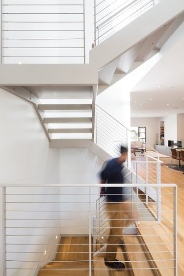 bright three-level staircase with light wood flooring and open layout