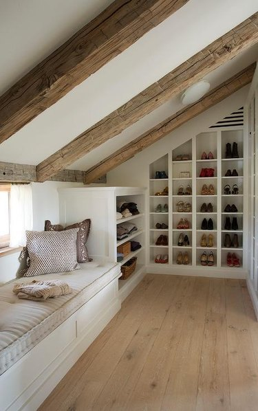 built-in attic storage in attic with exposed beams and window seat