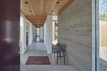 front door and entryway of minimal modern home with cement floors
