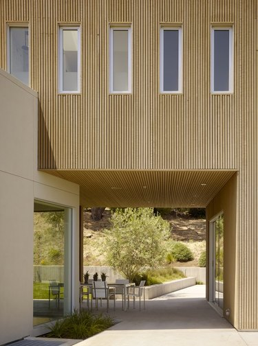 clean, minimal exterior with breezeway and outdoor dining set