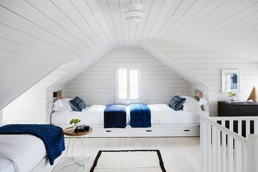 attic storage with white shiplap in kids' bedroom