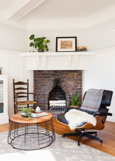 brick fireplace with eclectic vintage chairs and modern coffee table