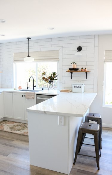 Farmhouse kitchen lighting with pendant light over sink in all-white kitchen