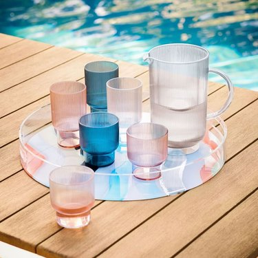 Blue, pink, and clear acrylic drinkware on round tray by the pool