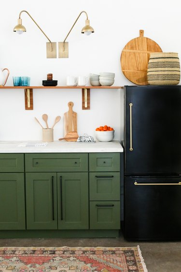 Brass wall sconces above open shelving for bohemian kitchen lighting