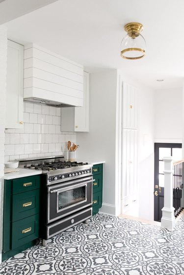 green kitchen cabinets with patterned floor tile an white walls