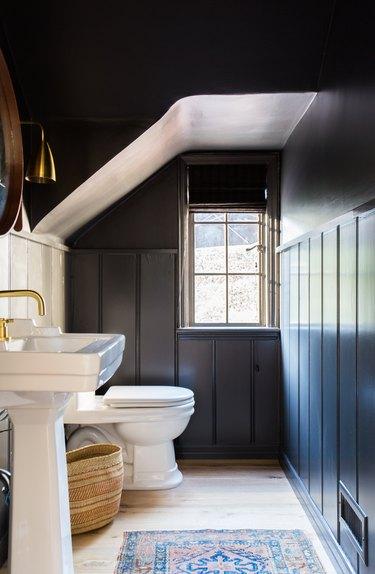 attic apartment bathroom with B=black walls, toilet, sink, brass fixtures, rug.