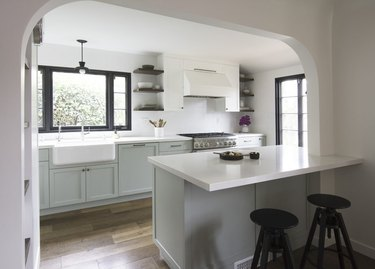green kitchen cabinets with white countertops and farmhouse sink