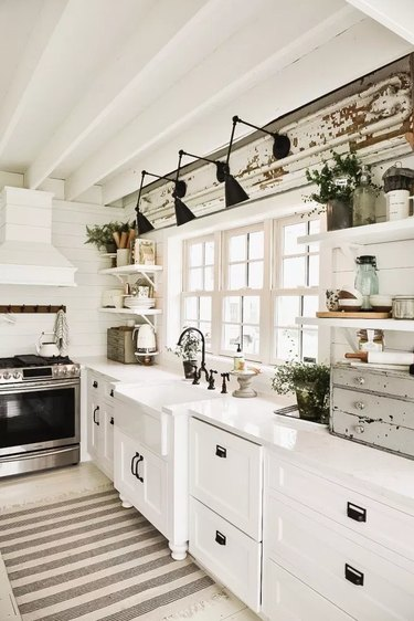 Farmhouse kitchen lighting with black wall sconces above apron sink