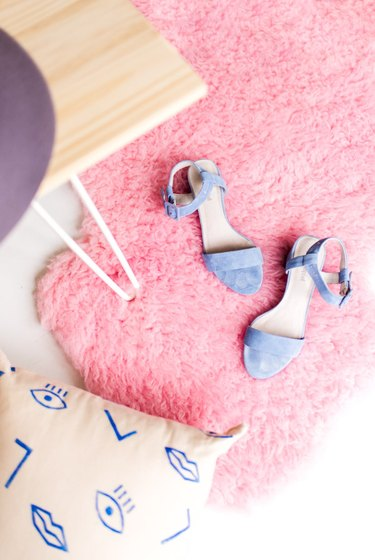 A pink rug with shoes on it